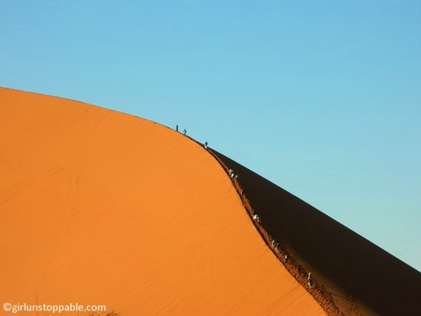 People climbing a sand dune in Sossusvlei, Namibia